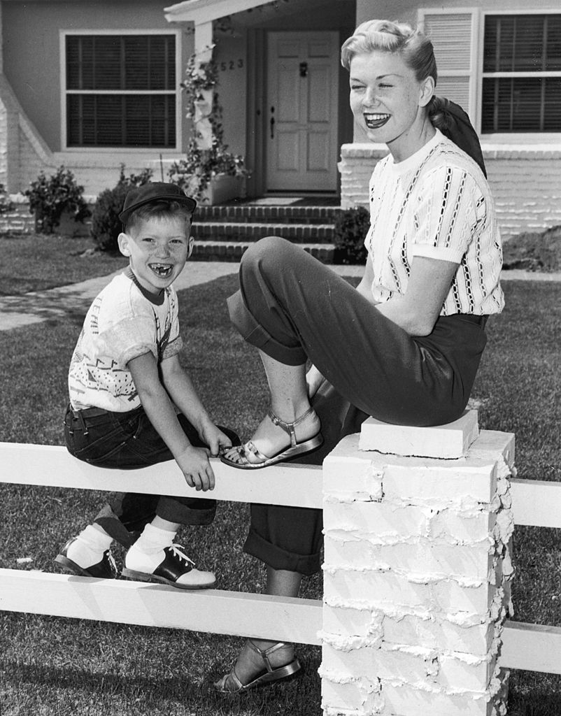 Image Credits: Getty Images / Hulton Archive | American actor and singer Doris Day smiles and laughs as she sits on a fence in front of a house with her son, Terry. Day wears sandals, trousers and has her hair tied back in a scarf.