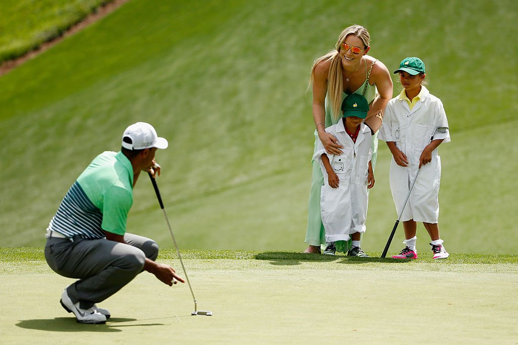 Image Credits: Getty Images / Ezra Shaw | Tiger Woods of the United States waits a green as his girlfriend Lindsey Vonn, son Charlie and daughter Sam look on during the Par 3 Contest prior to the start of the 2015 Masters Tournament at Augusta National Golf Club on April 8, 2015 in Augusta, Georgia.