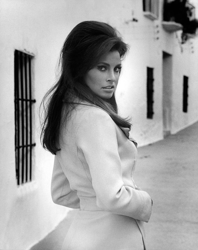 Image Source: Getty Images| Raquel posing wearing a trench coat