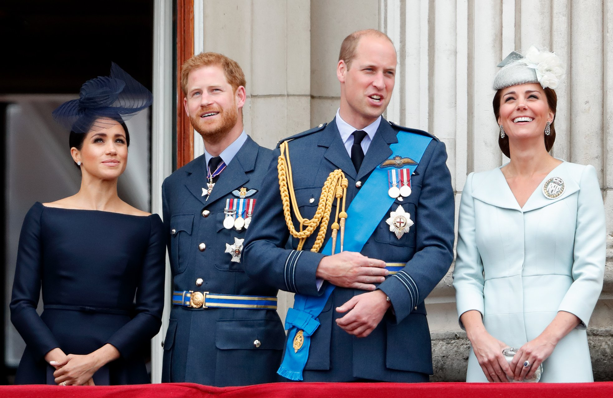 Image Credits: Getty Images / Max Mumby / Indigo   Meghan, Duchess of Sussex, Prince Harry, Duke of Sussex, Prince William, Duke of Cambridge and Catherine, Duchess of Cambridge watch a flypast to mark the centenary of the Royal Air Force from the balcony of Buckingham Palace on July 10, 2018 in London, England. The 100th birthday of the RAF, which was founded on on 1 April 1918, was marked with a centenary parade with the presentation of a new Queen's Colour and flypast of 100 aircraft over Buckingham Palace.
