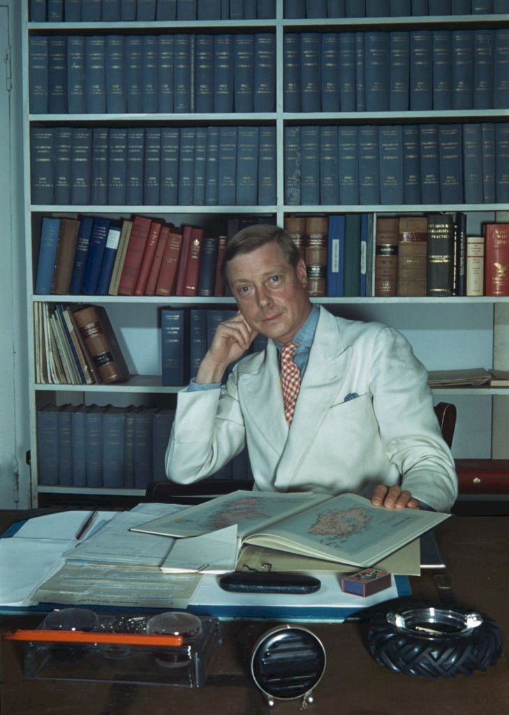 Image Credits: Getty Images / Ivan Dmitri / Michael Ochs Archives | The Duke of Windsor (1894-1972) sitting at a desk, which is strewn with books and paperwork in Goverment House in Nassau, the Bahamas, circa 1942.