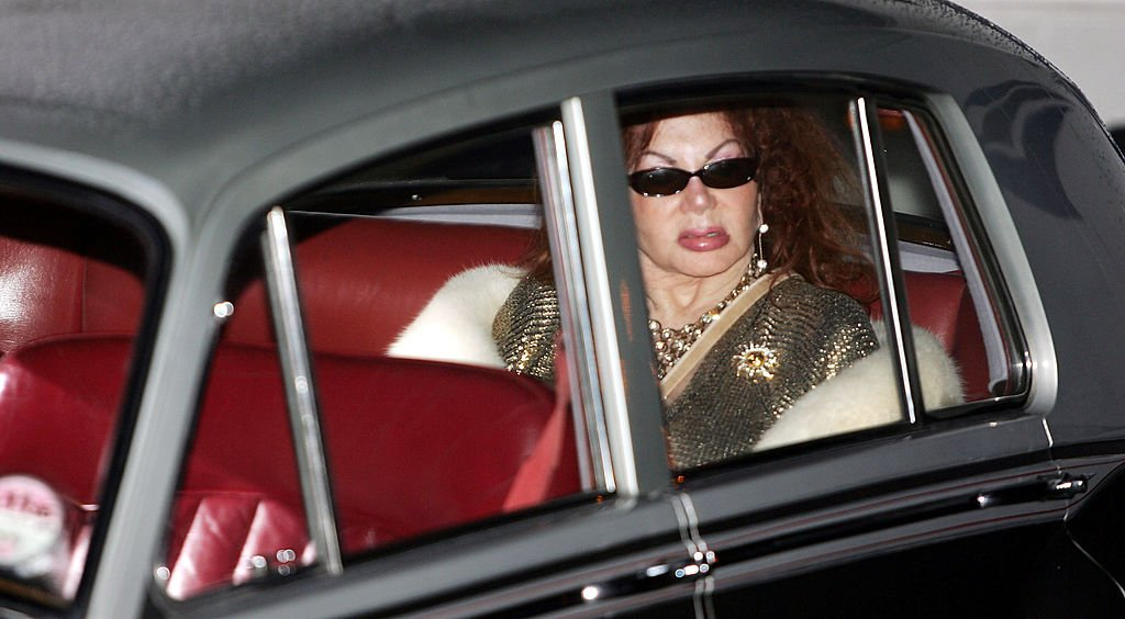 Image Credits: Getty Images / Gareth Cattermole | Celebrity Big Brother III housemate Jackie Stallone poses for photographs outside the Big Brother house, before her surprise entry to the house at Elstree Studios on January 10, 2004 in Hertfordshire, England.