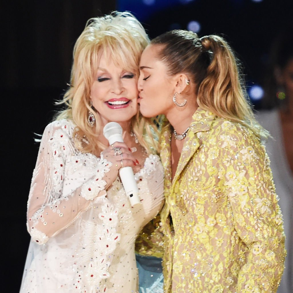 Image Credits: Getty Images / Kevin Winter | Dolly Parton (L) and Miley Cyrus perform onstage during the 61st Annual GRAMMY Awards at Staples Center on February 10, 2019 in Los Angeles, California.