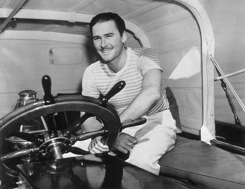 Image Source: Getty Images / Australian-born actor Errol Flynn (1909-1959) smiles as he sits with one hand on the captain's wheel of a yacht.