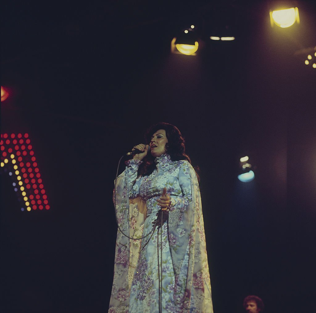 Image Credit: Getty Images / Photo of Loretta Lynn performing on stage.