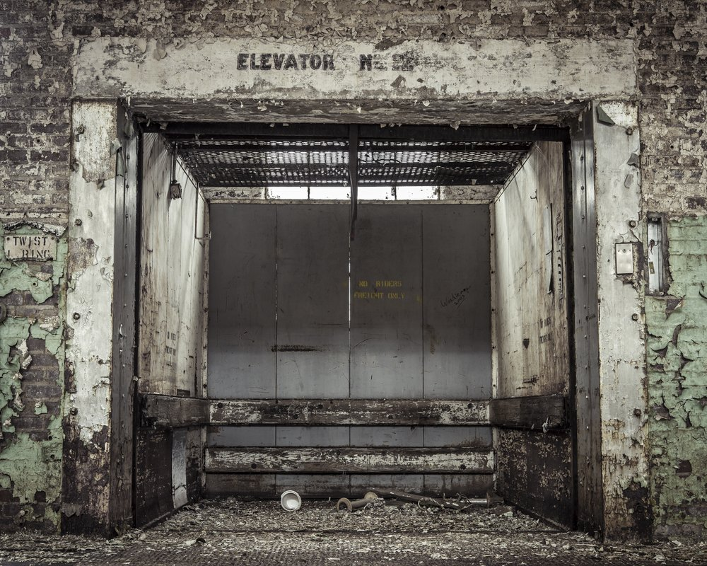 Grungy industrial elevator in an abandoned building | Shutterstock