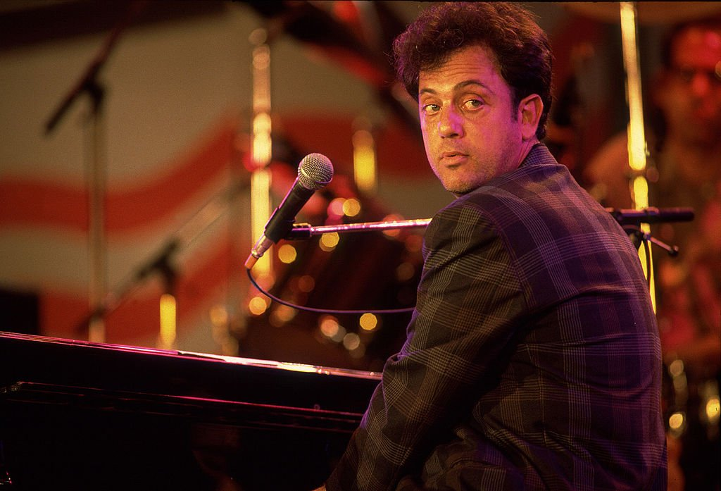 Image Credits: Getty Images / Paul Natkin | Musician Billy Joel performs onstage during the first Farm Aid benefit concert at Memorial Stadium, Champaign, Illinois, September 22, 1985.