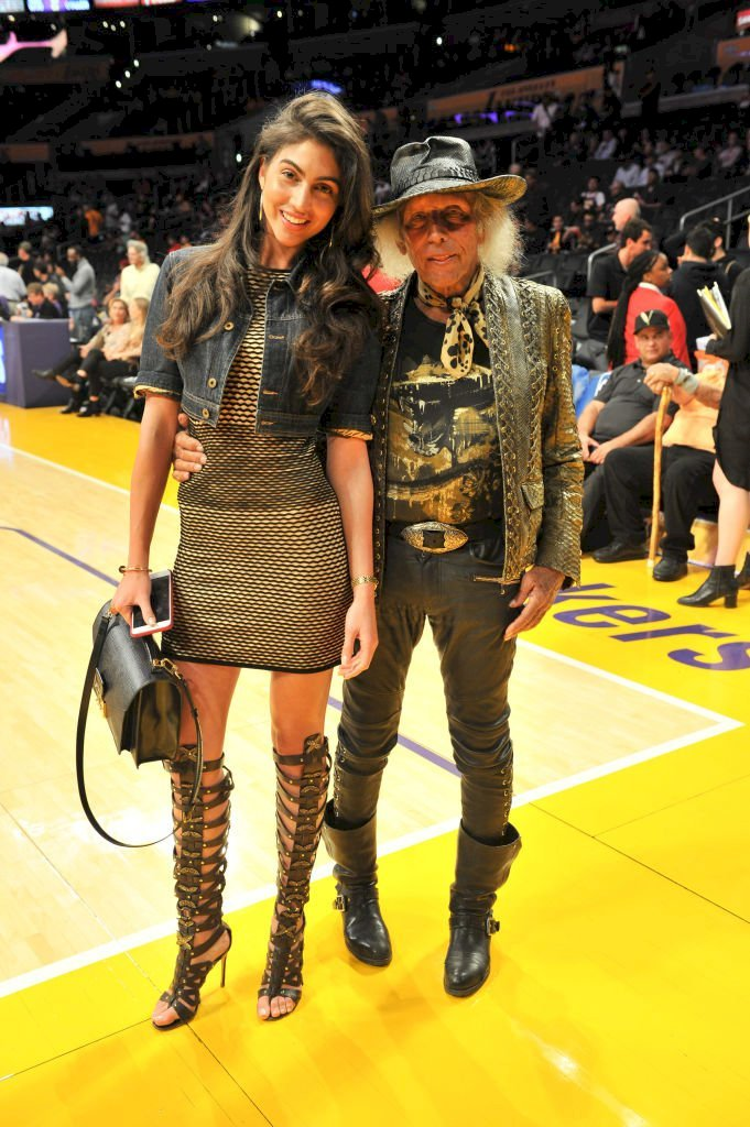 Image Credits: Getty Images / Allen Berezovsky | Jimmy Goldstein (R) and model Simone Aptekman attend a basketball game between the Los Angeles Lakers and the Philadelphia 76ers at Staples Center.