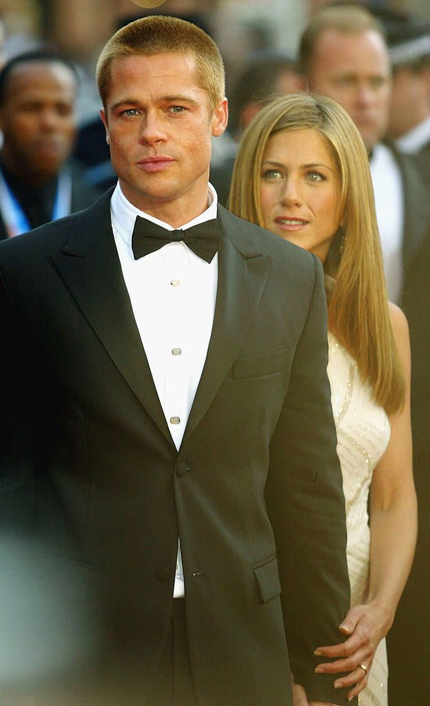 "Image Credits: Getty Images / Bruno Vincent | Brad Pitt and Jennifer Aniston attend the World Premiere of epic movie ""Troy"" at Le Palais de Festival on May 13, 2004 in Cannes, France."