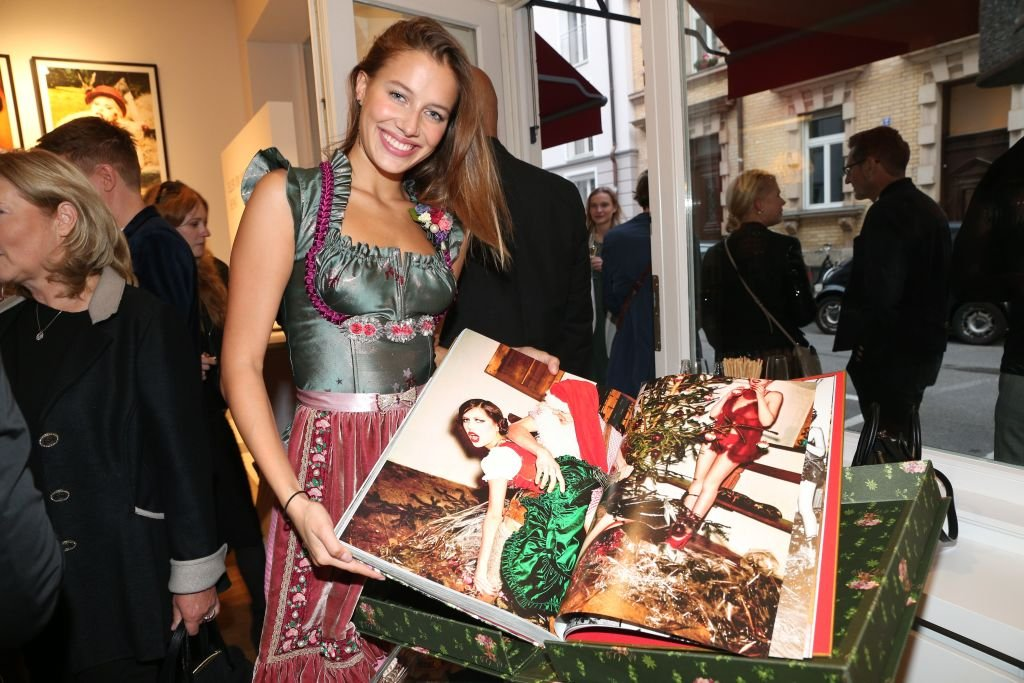 Image Credit: Getty Images/Gisela Schober | Nicole Poturalski (Nico Mary) shows her photo ind the book during the 'Ellen von Unwerth: HEIMAT' Exhibition