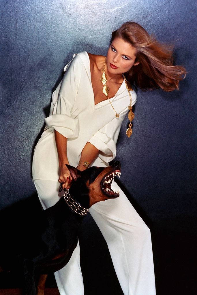 Image Credits: Getty Images / Chris von Wangenheim / Conde Nast | Model Christie Brinkley, wearing a white silk crepe pajama by Geoffrey Beene, and a gold leaf necklace by Mary McFadden, while restraining a Doberman Pinscher on a leash.
