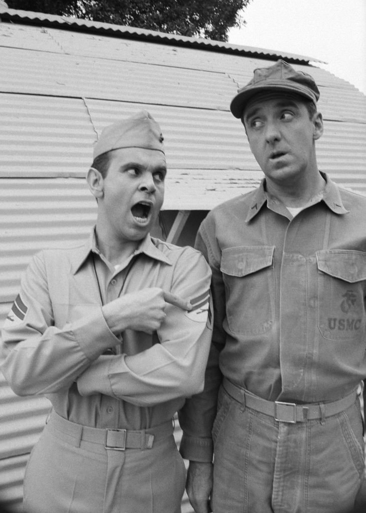 Image Source: Getty Images/CBS Photo Archive| American actors Ronnie Schell (left, as Pvt. Gilbert 'Duke' Slater) and Jim Nabors (as Pvt. Gomer Pyle) stand outside a Quonset hut during the filming of an episode of the television comedy series