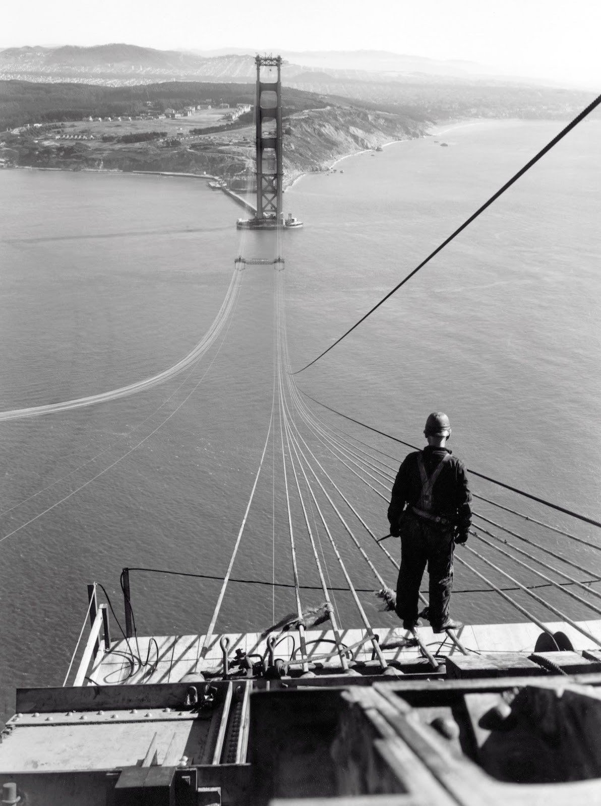 A man stands on the first cables of the Golden Gate Bridge during its construction,1935. Image Source: YouTube/Medium