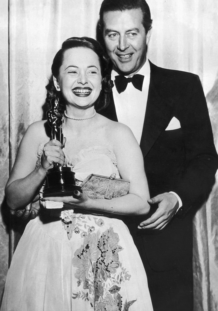 Image Credits: Getty Images / Keystone | Olivia de Havilland receives her Best Actress Oscar from actor Ray Milland