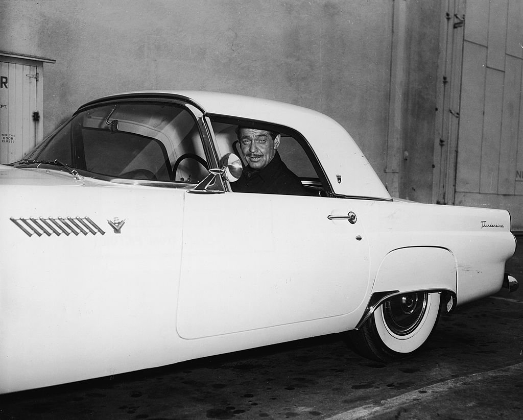 Image Credit: Getty Images / American actor Clark Gable sits in his 1955 Ford Thunderbird sports car and smiles, late 1950s.