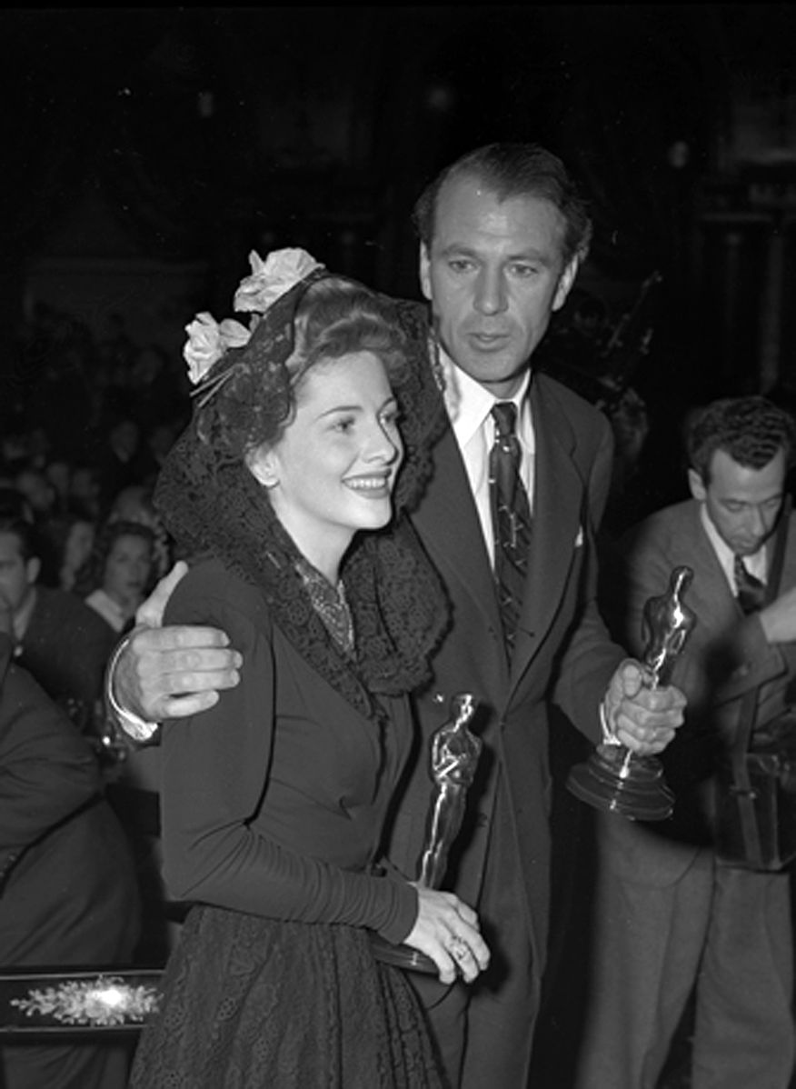 Image Source: Wikimedia Commons/Actors Joan Fontaine and Gary Cooper holding their Oscars at the Academy Awards after party, 1942