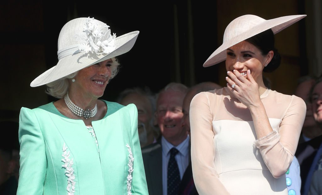 Image Credits: Getty Images / Chris Jackson   (L-R) Camilla, Duchess of Cornwall and Meghan, Duchess of Sussex attend The Prince of Wales' 70th Birthday Patronage Celebration held at Buckingham Palace on May 22, 2018 in London, England.