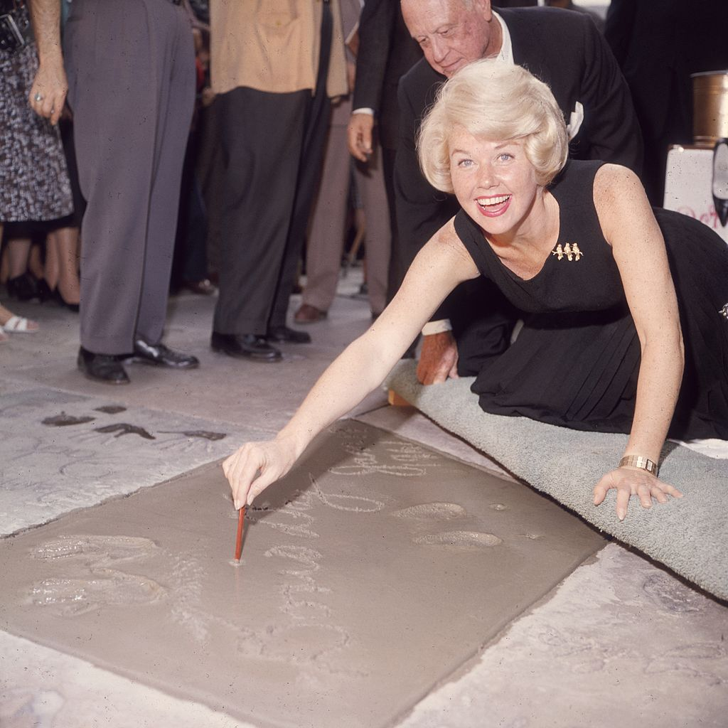 Image Credits: Getty Images / Hulton Archive | American singer and actress Doris Day smiling as she signs her name in cement by her handprints, in front of Mann's (formerly Grauman's) Chinese Theater, on Hollywood Boulevard, Hollywood, California.