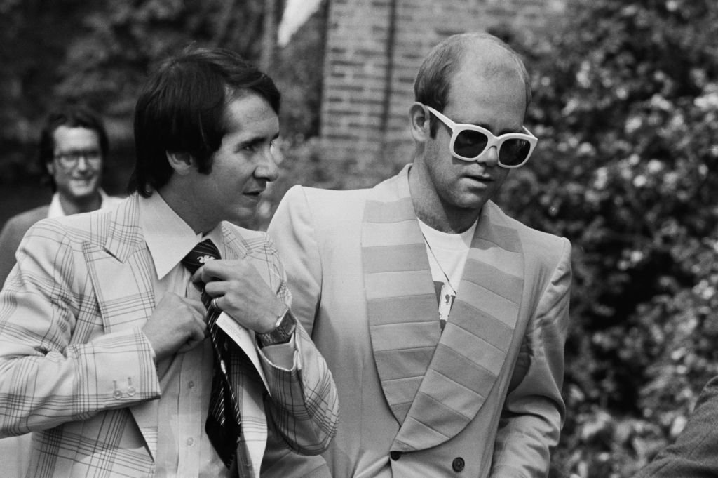 Image Credit: Getty Images / English singer, songwriter, pianist, and composer Elton John and his manager John Reid on their way to a luncheon in honour of Buddy Holly at the Orangery in Holland Park.