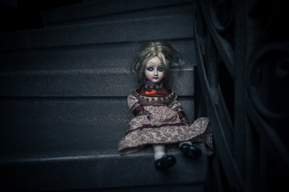 Creepy porcelain doll on stairs | Shutterstock