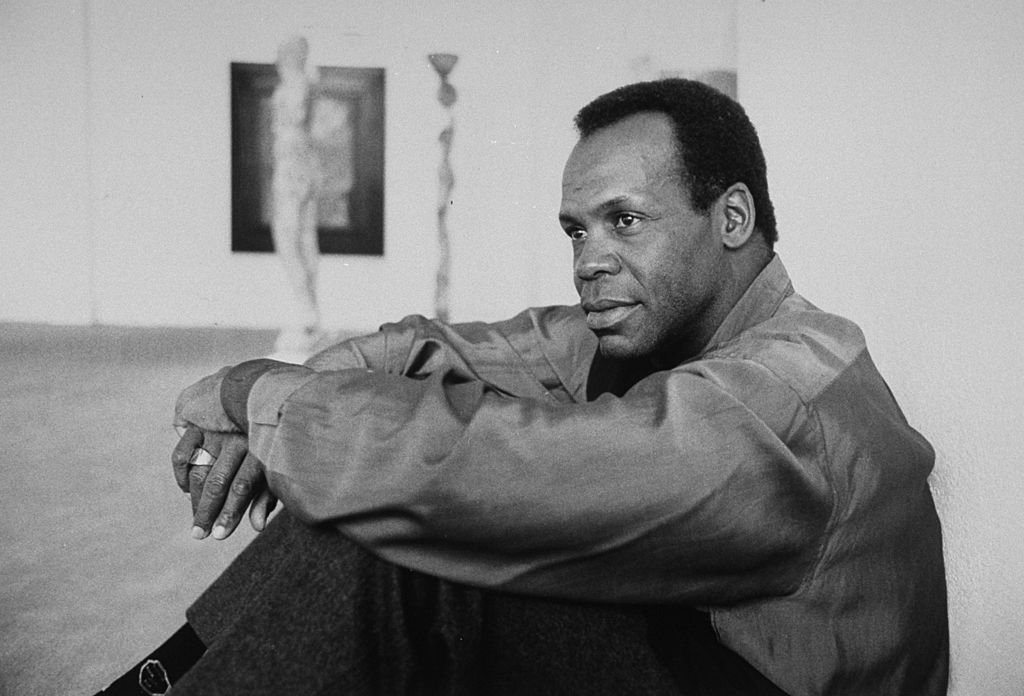 Image Source: Getty Images/Kim Komenich| Actor Danny Glover sitting on floor in art gallery