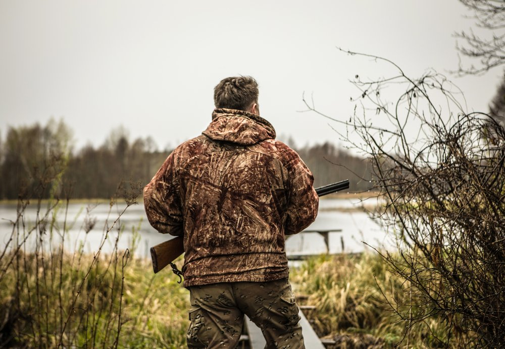 Hunter with a gun tracks down ducks on the river. | Shutterstock