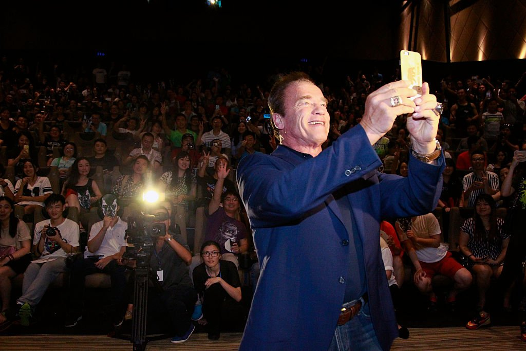 Image Credits: Getty Images / Kevin Lee | Arnold Schwarzenegger takes a selfie with audience at the first screenings of Terminator Genisys at Palace IAPM on August 22, 2015 in Shanghai, China.