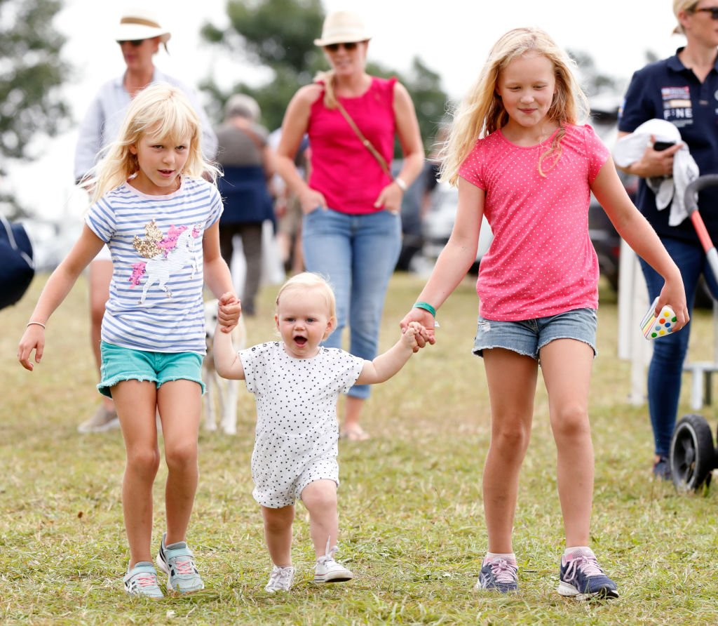 Image Credit: Getty Images / Isla Phillips (l) and Savannah Phillips (r) walk holding hands with their cousin Lena Tindall at Gatcombe Park on August 4, 2019 in Stroud, England.