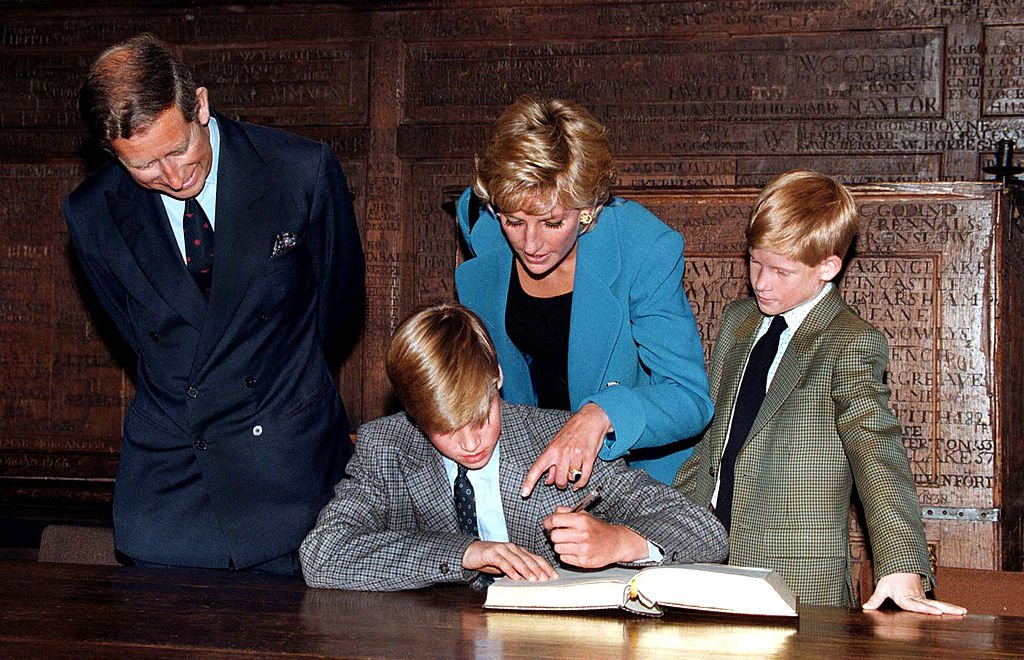 Image Credit: Getty Images / Prince William follows Eton tradition by signing a book before starting at the school, as Prince Charles, Princess Diana (1961 - 1997) and Prince Harry look on, September 1995.
