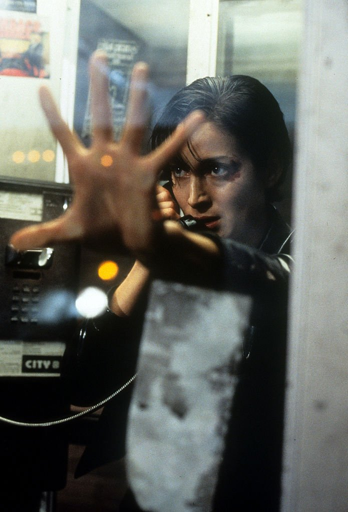 Image Credits: Getty Images / Warner Brothers | Carrie-Anne Moss in phone booth in a scene from the film 'The Matrix', 1999.