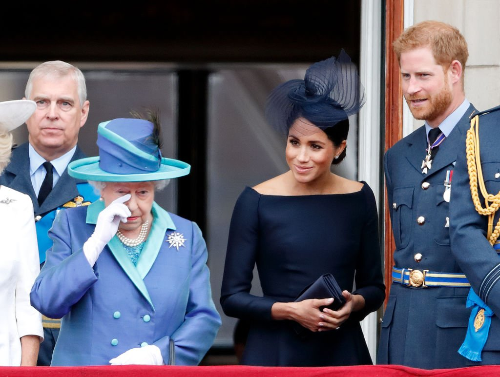 Image Credit: Getty Images / Queen Elizabeth II, Meghan, Duchess of Sussex and Prince Harry, Duke of Sussex watch a flypast to mark the centenary of the Royal Air Force from the balcony of Buckingham Palace on July 10, 2018 in London, England.