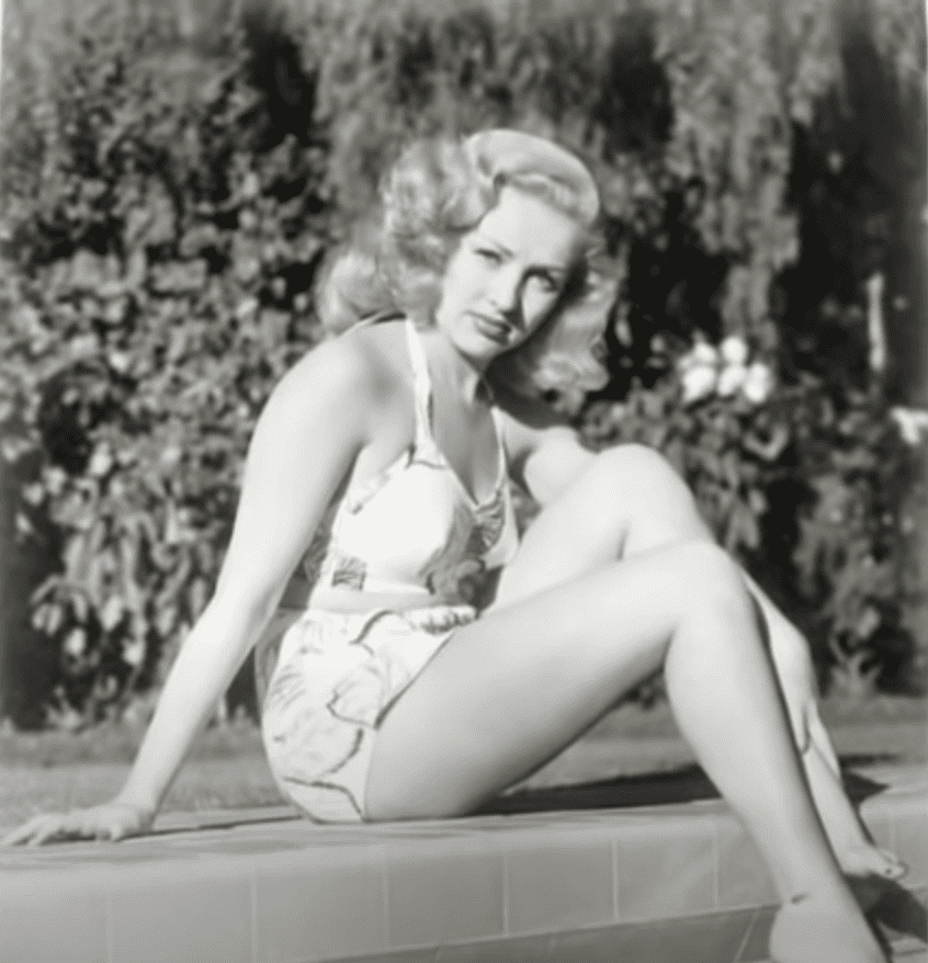 Image Source: Youtube/Stacey| Betty posing beside the pool