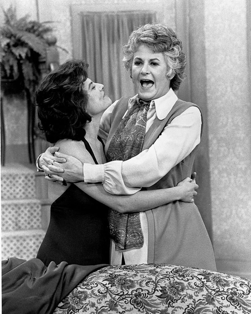 Image Credits: Getty Images / CBS Photo Archive | American actresses Adrienne Barbeau and Bea Arthur hug each other in a scene from the tv sitcom 'Maude,' 1972. Barbeau played Carol, the daughter of the title character portrayed by Arthur.