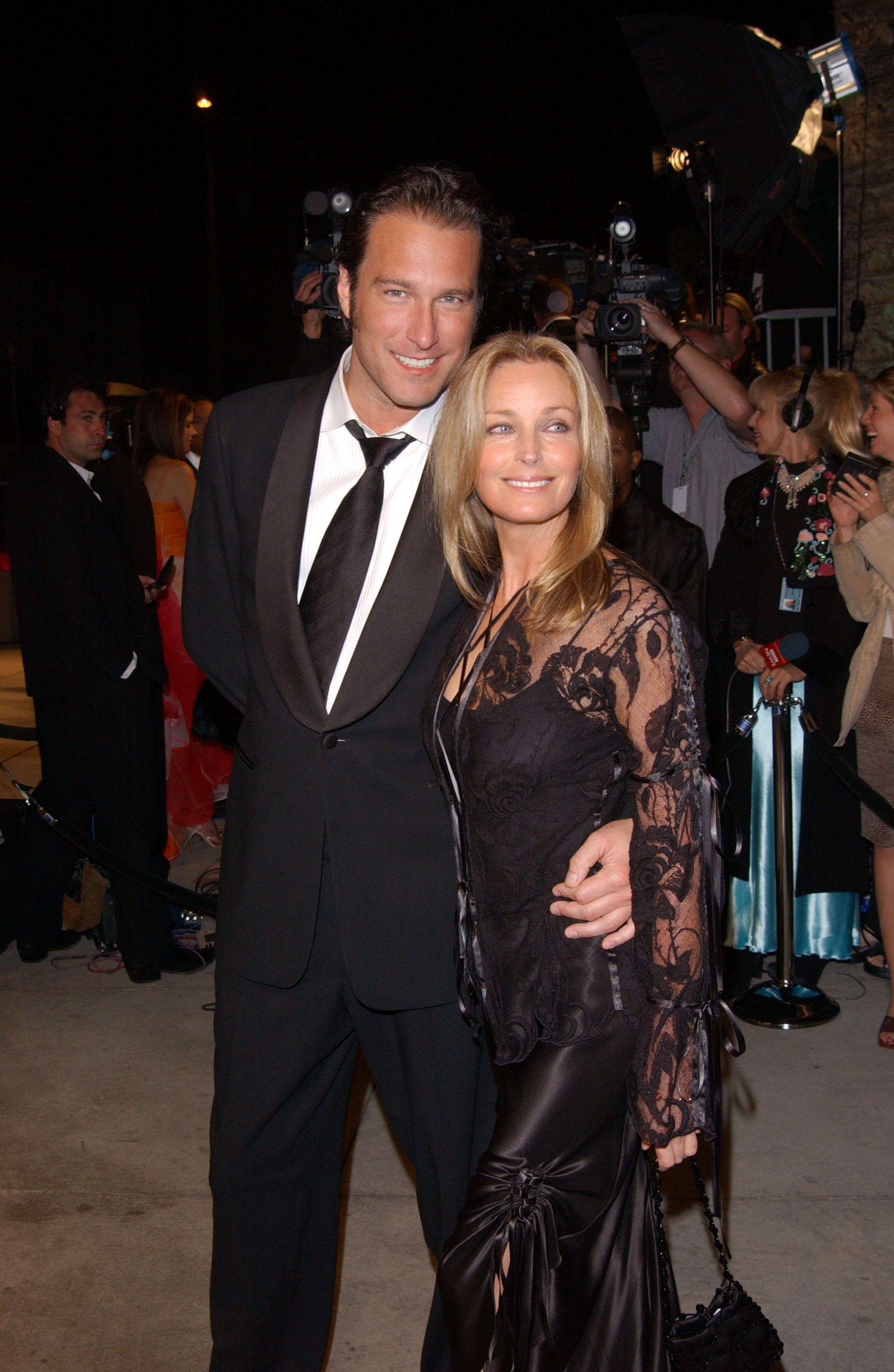 Image Credits: Getty Images / The model and Hollywood actor Bo Derek and John Corbett are photographed by the press.
