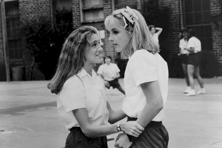 Image Credits: Getty Images / New World Pictures | Sarah Jessica Parker and Helen Hunt on the playground of their all girls Catholic school in a scene from the film 'Girls Just Want To Have Fun', 1985.