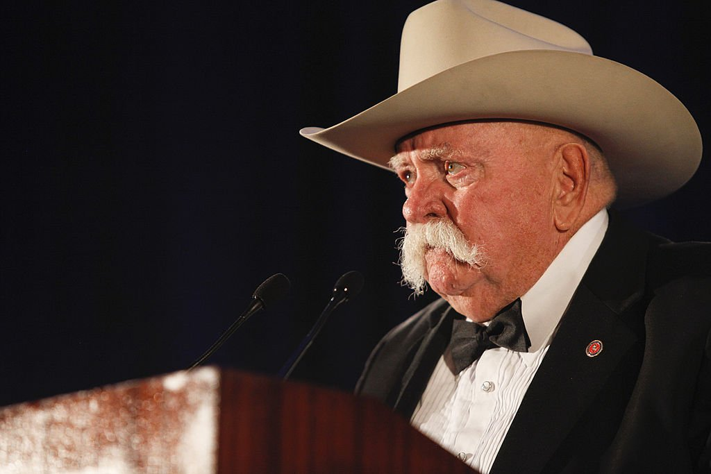 Image Source: Getty Images/Imeh Akpanudosen| Actor Wilford Brimley speaks on stage at the 50th Anniversary Stuntmens Gala Honoring Harrison Ford on September 24, 2011 in Universal City, California