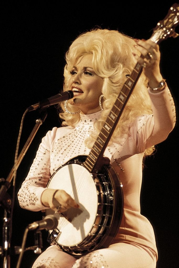 Image Credits: Getty Images / Andrew Putler / Redferns | Photo of Dolly Parton, performing live onstage at the UK Country Music Festival, playing banjo.