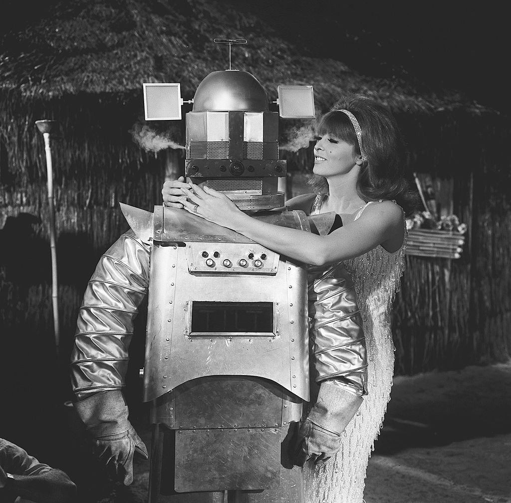 Image Credit: Getty Images / American actress Tina Louise, as Ginger, wraps her arms around the 'shoulders' of a robot (played by Bob D'Arcy) in a scene from an episode of the television comedy 'Gilligan's Island' entitled 'Gilligan's Living Doll,' Los Angeles, California, November 18, 1965.