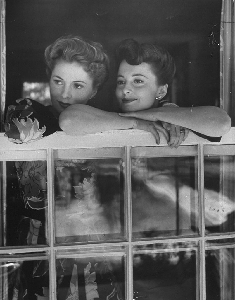 Image Credits: Getty Images / Bob Landry/The LIFE Picture Collection | Actress Joan Fontaine and Olivia De Havilland looking out top of open window at her home