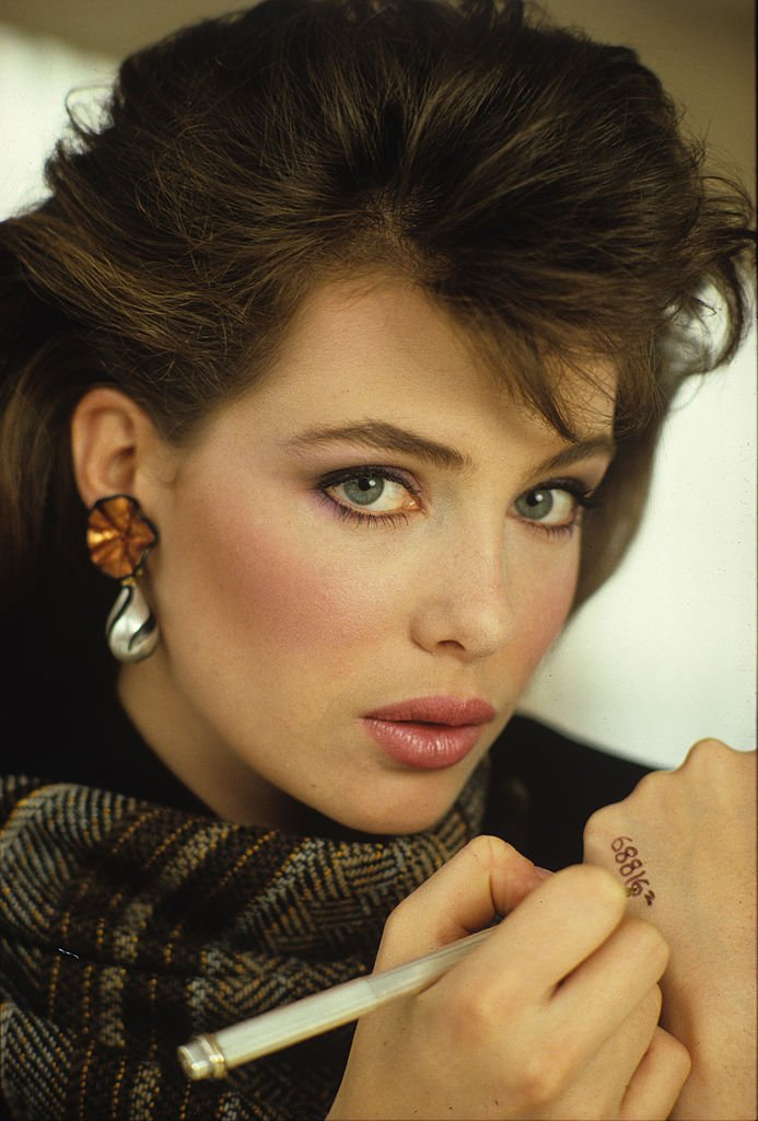 Image Credits: Getty Images / Andrea Blanch | Close-up portrait of American actress and model Kelly LeBrock as she writes a telephone number on her hand during a magazine photoshoot, early 1980s.