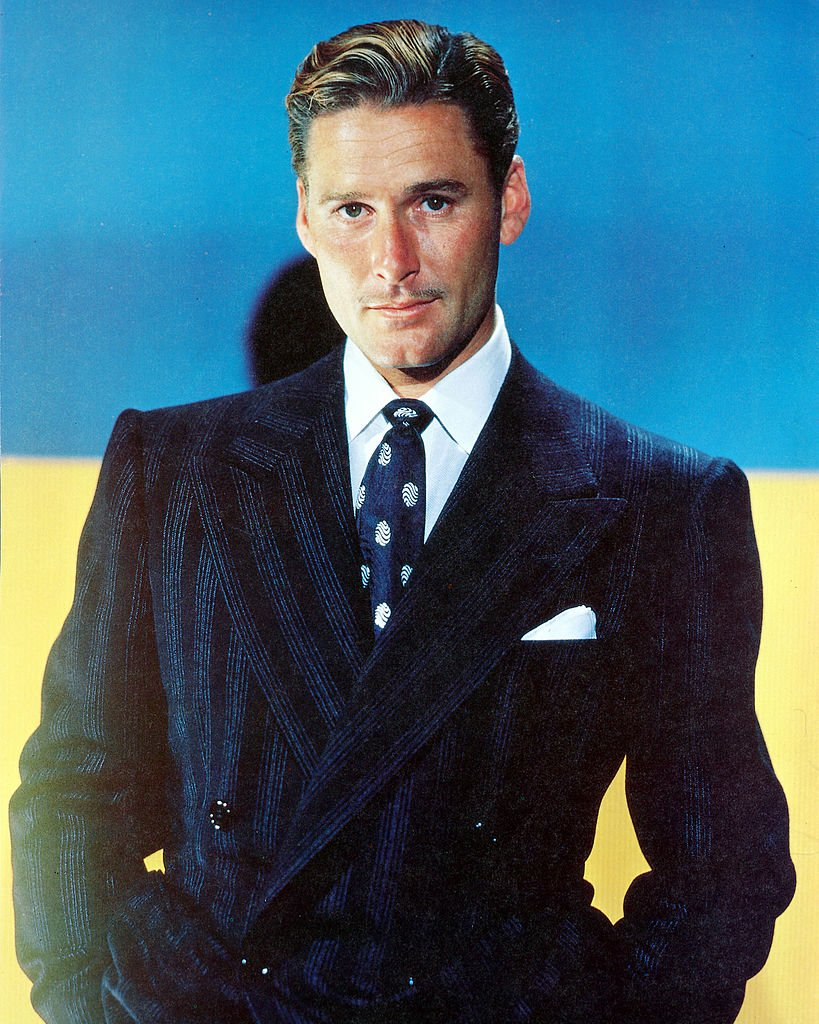 Image Source: Getty Images/Silver Screen Collection/Errol Flynn (1909-1959), Australian actor, wearing a dark blue jacket, white shirt, and blue tie with white motifs in a studio portrait, with a blue background, circa 1945