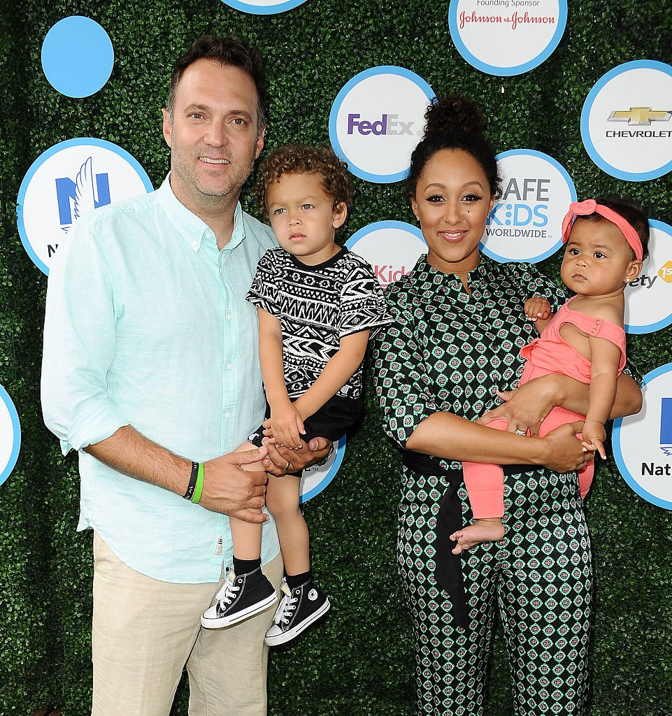 Image Credits: Getty Images / Jason LaVeris / FilmMagic | Adam Housley, Aden John Tanner Housley, Tamera Mowry and Ariah Talea Housley attend Safe Kids Day at Smashbox Studios on April 24, 2016 in Culver City, California.