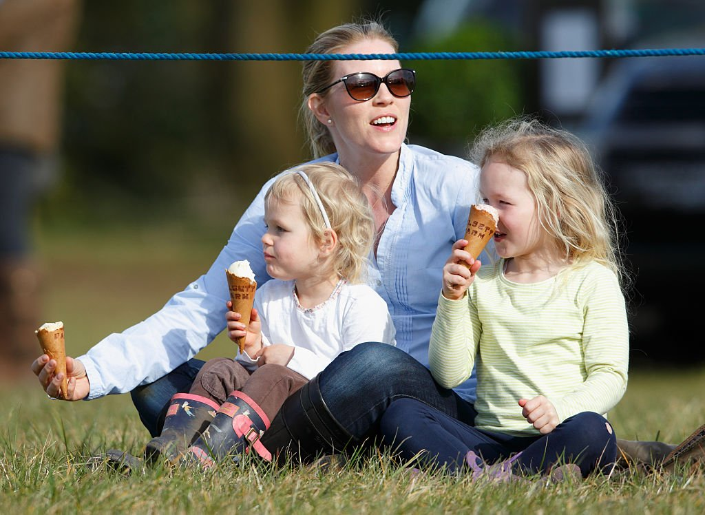 Image Credit: Getty Images / Autumn Phillips and daughters Isla Phillips (l) and Savannah Phillips (r) eat ice creams as they watch the show jumping on March 25, 2016 in Stroud, England.