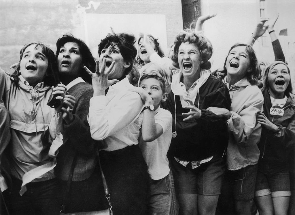 Image Credits: Getty Images / Fox Photos | Women and girls in Toronto, Canada screaming with joy during a visit by the Beatles to their city.