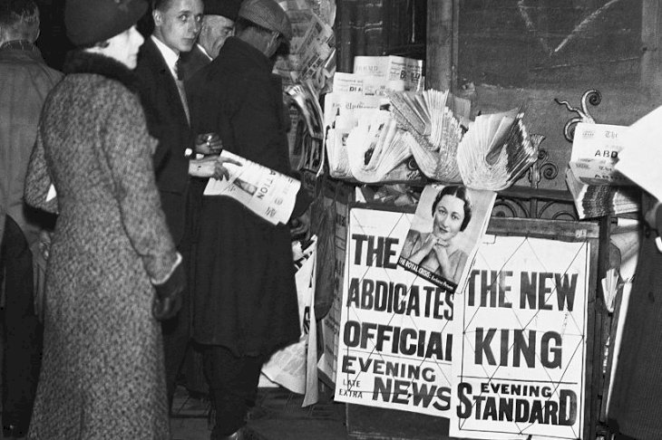 Image Credits: Getty Images / Hulton-Deutsch Collection / CORBIS | People surround a newspaper stand in Parliament Square, London, to read the news of King Edward VIII's abdication.