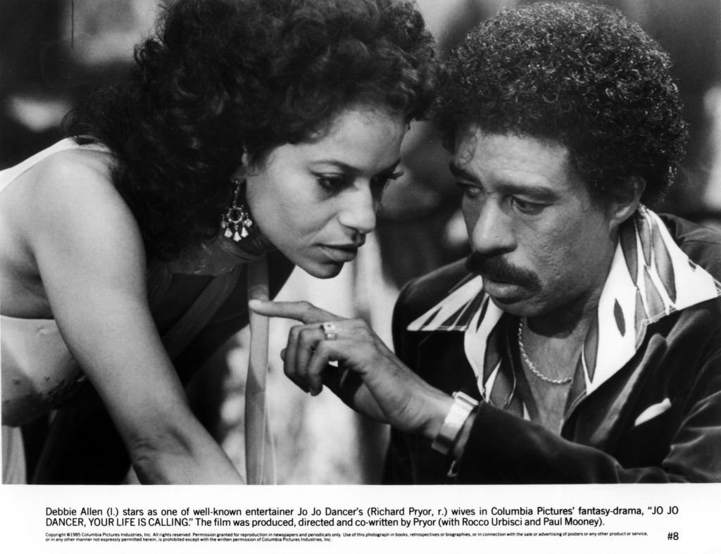 "Image Credits: Getty Images / Michael Ochs Archives | Richard Pryor and actress Debbie Allen in a scene from the movie ""Jo Jo Dancer, Your Life Is Calling"""