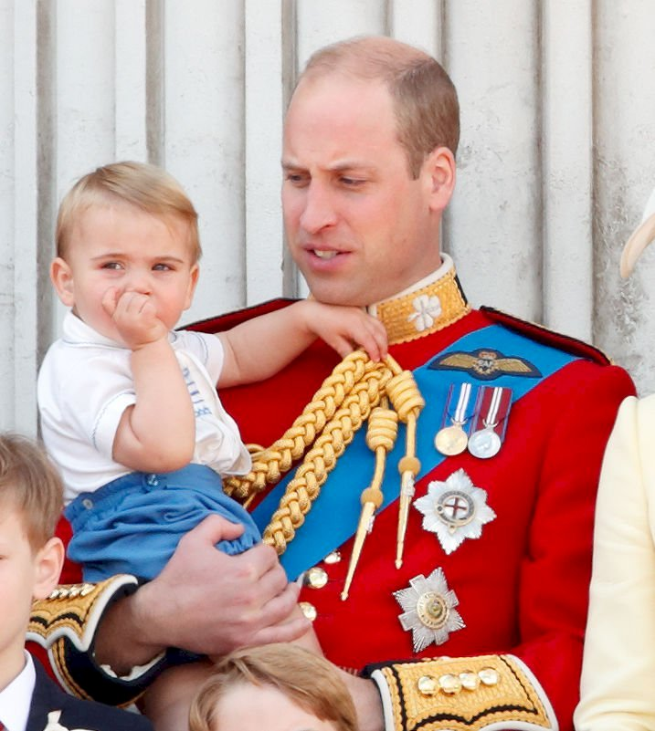 Image Credit: Getty Images / Prince William, Duke of Cambridge and Prince Louis of Cambridge watch a flypast from the balcony of Buckingham Palace during Trooping The Colour.