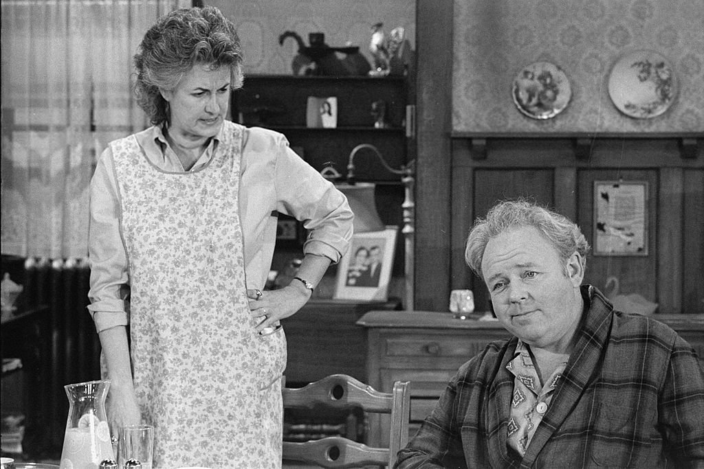 Image Credits: Getty Images / CBS Photo Archive | American actress Bea Arthur (as Maude Findlay) looks angrily at American actor Carroll O'Connor (1924 - 2001) (as Archie Bunker) in a scene from an episode of the controversial CBS sitcom 'All in the Family' entitled 'Cousin Maude's Visit,' Los Angeles, November 9, 1971. The episode first aired on December 11, 1971. The series, which concerned the domestic antics of O'Connor as a Queens, New York, bigot, aired from 1971 to 1979. Arthur's character got her own spin-off series called 'Maude' which ran from 1972 to 1978.