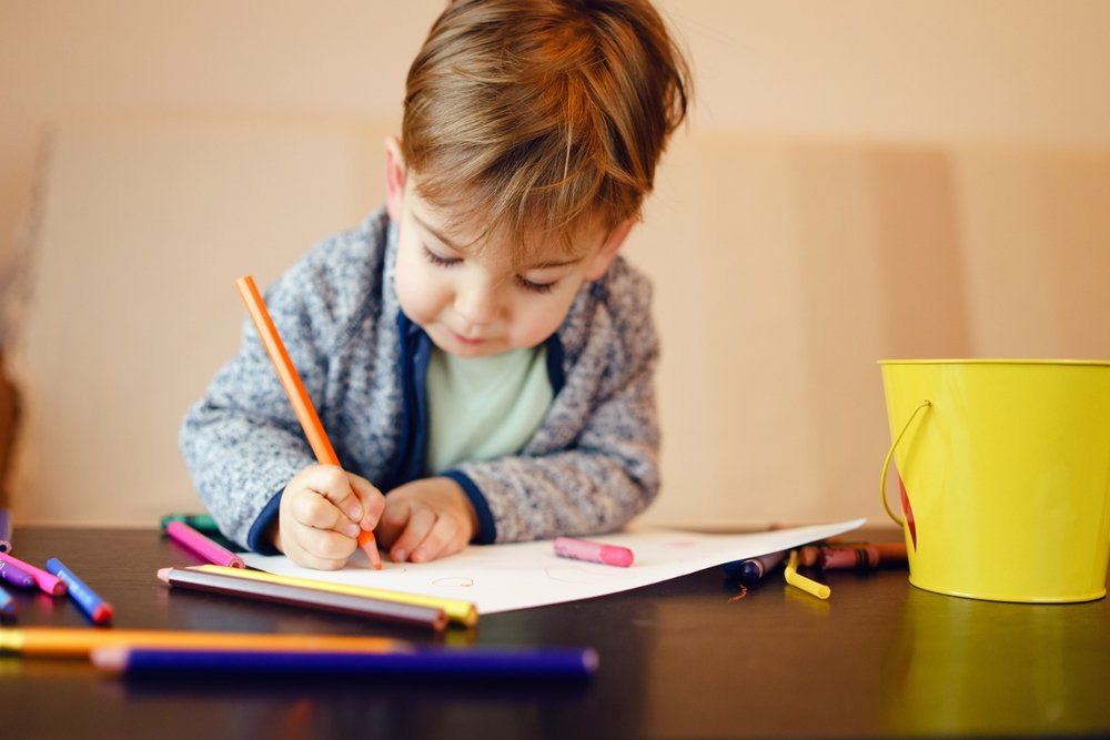 Young boy plays with crayons at table | Shutterstock