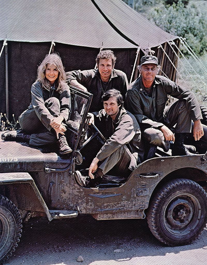 Image Credits: Getty Images / Keystone | Alan Alda in the driving seat of a jeep, surrounded by Loretta Swit and other cast members of M.A.S.H